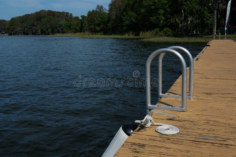 Ein Dock an einem See mit einer Leiter und einem Bügelen stockfotos