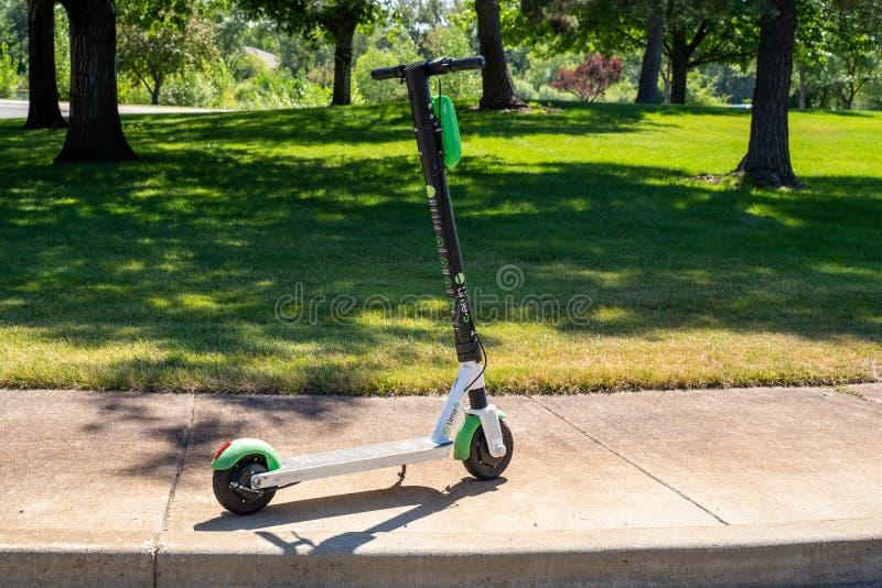 Ein dockless elektronischer Roller der Kalkmarke sitzt auf einem Bürgersteig, unbeaufsichtigt Diese app-ansässigen Roller stockbild