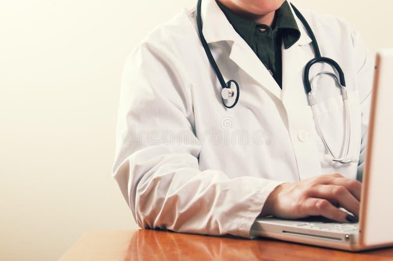 Ein Doktor, der einen Computerlaptop verwendet stockbilder