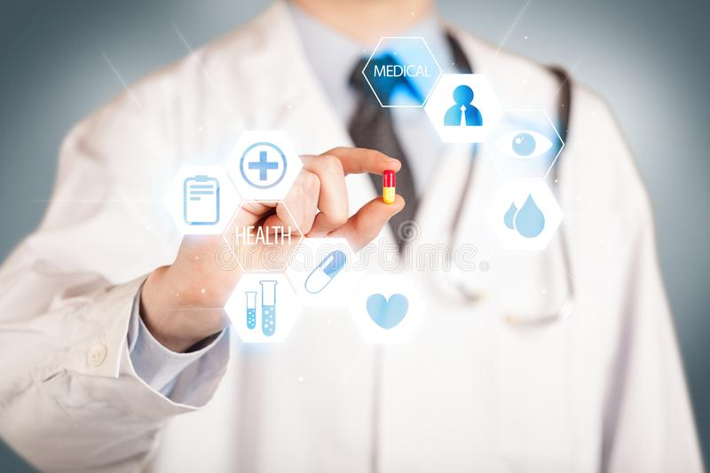 Ein Doktor im Weiß, das eine Pille hält stockfotografie