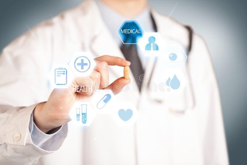 Ein Doktor im Weiß, das eine Pille hält lizenzfreies stockbild