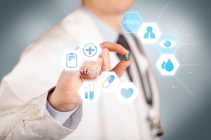 Ein Doktor im Weiß, das eine Pille hält stockfoto
