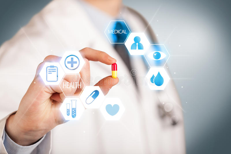 Ein Doktor im Weiß, das eine Pille hält lizenzfreie stockfotos