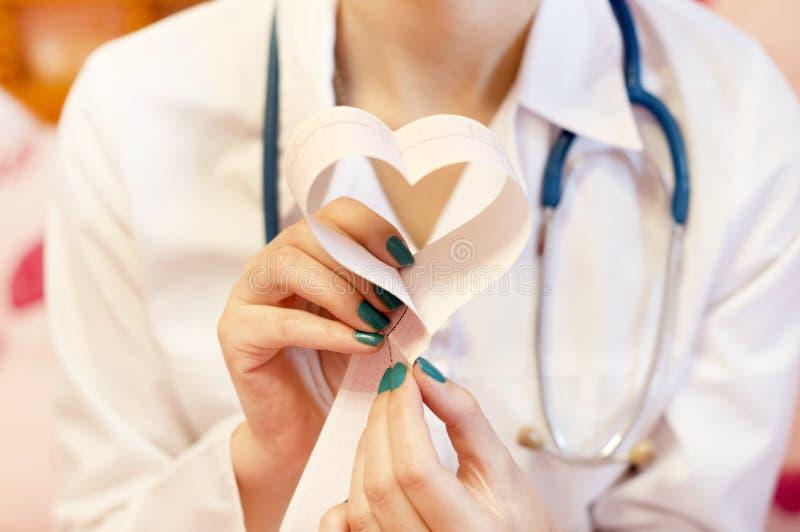 Ein Doktor mit Kardiogrammen in seinen Händen in Form eines Herzens lizenzfreies stockbild