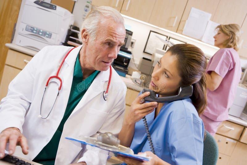 Ein Doktor und eine Krankenschwester an der Aufnahme stockbild