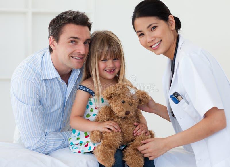 Ein Doktor und ihr Patient, die einen Teddybären überprüfen stockbilder