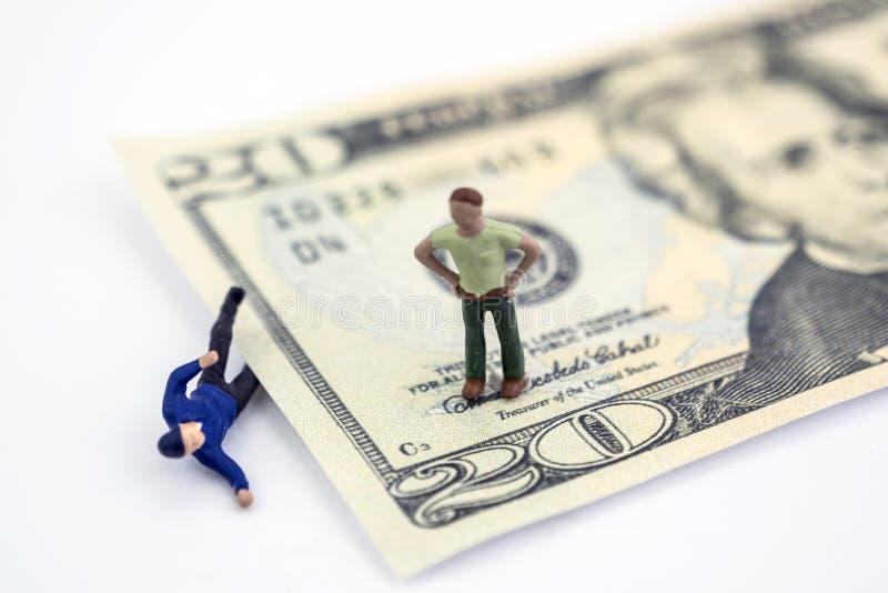 Ein Dollarschein zerquetscht einen Miniaturmann, einen Mann über dem Schauen lizenzfreies stockbild