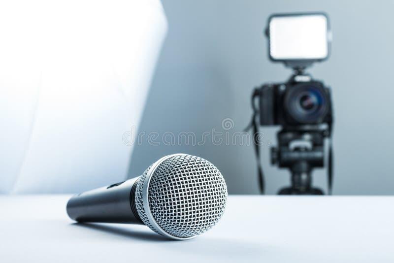 Ein drahtloses Mikrofon, das auf einer Studiotabelle vor dem hintergrund der DSLR-Kamera zu geführtem Licht und zu softbox liegt stockbild