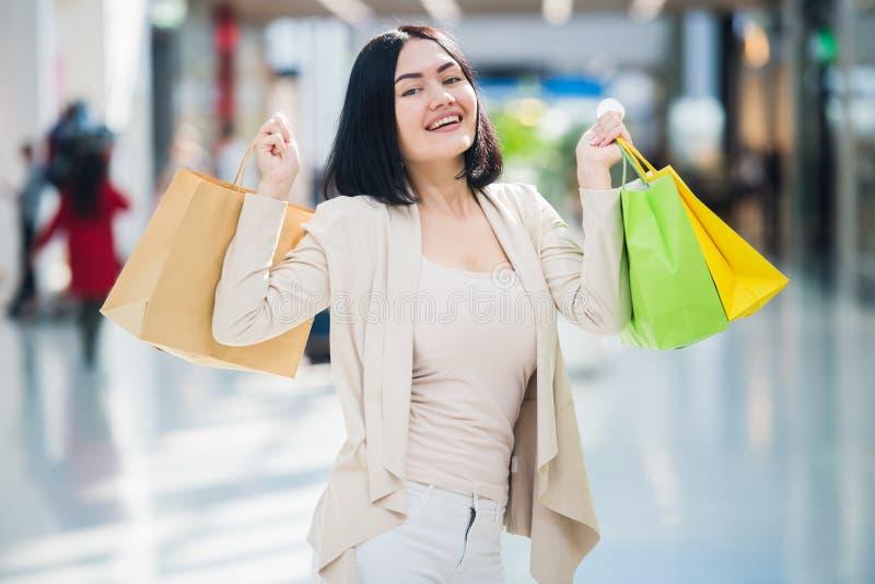 Ein dunkelhaariges Frauentragen gedämpft, leichte Farben hält die bunten, kopierten Einkaufstaschen geht an einem Exklusiven stockbilder