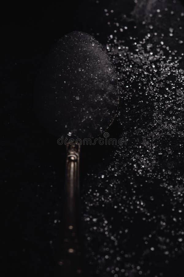 Ein dunkles Foto eines Löffels mit raffiniertem Zucker auf einem schwarzen Steinhintergrund mit Kopienraum, Draufsicht, zurückhal stockbild