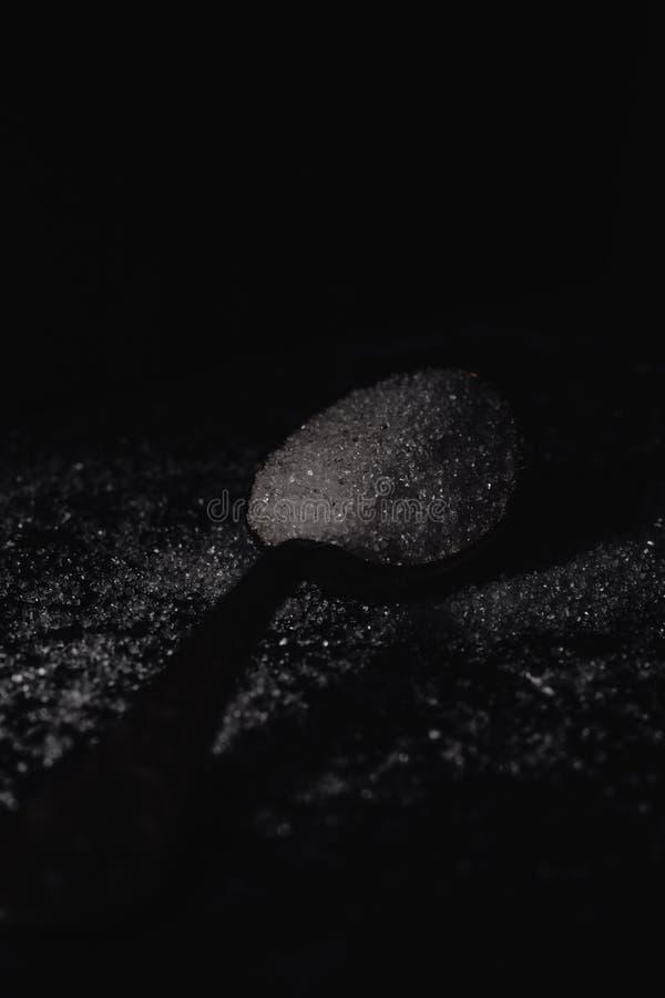 Ein dunkles Foto eines Löffels mit raffiniertem Zucker auf einem schwarzen Steinhintergrund mit Kopienraum, horizontale Ansicht,  lizenzfreie stockfotografie