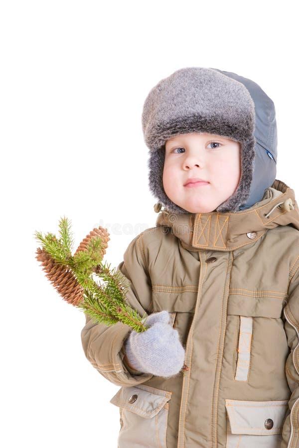 Ein durchdachter Junge im Wintermantel mit einem Zweig von f stockfoto