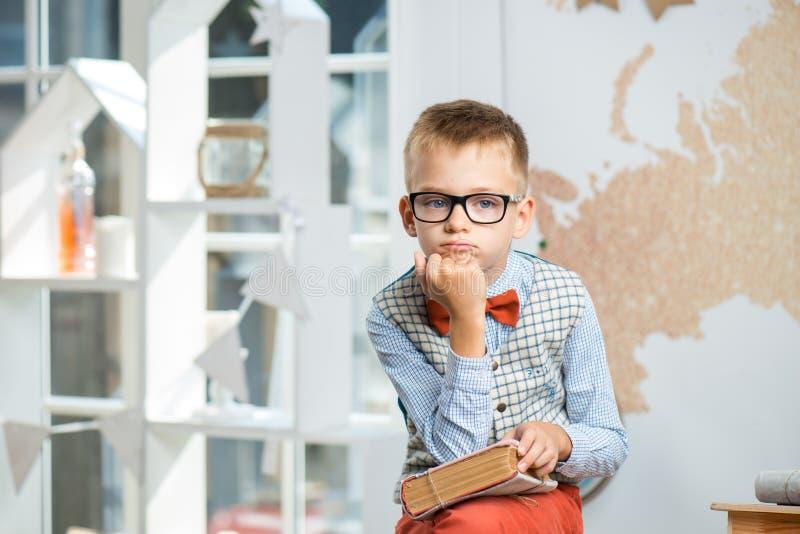 Ein durchdachter Schüler sitzt an einem Schreibtisch mit Büchern lizenzfreie stockfotos