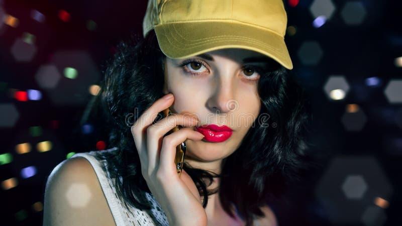 Ein ehrfürchtiger junger Brunette in einer gelben Kappe lizenzfreie stockbilder