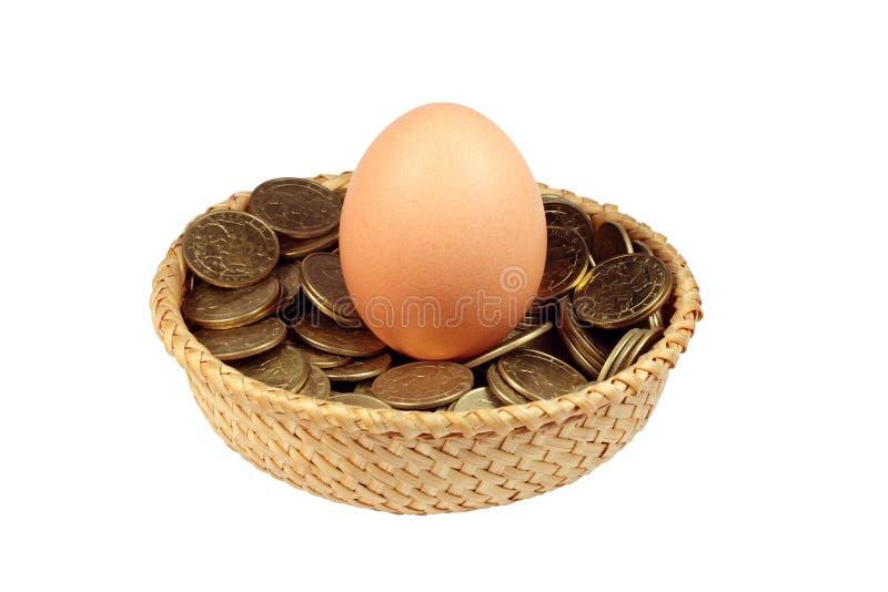 Ein Ei und Münzen in einem Korb lizenzfreie stockfotos