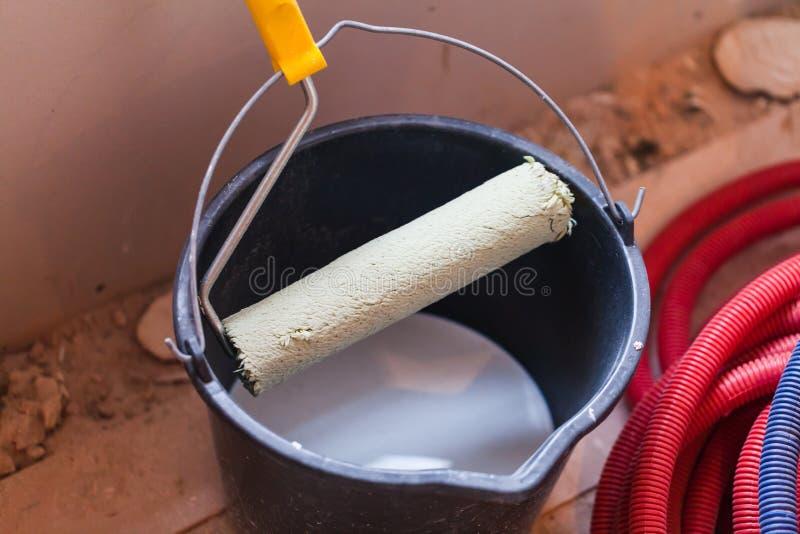 Ein Eimer mit weißer Farbe und einer Rolle auf einer Wohnung ist im Bau stockfoto