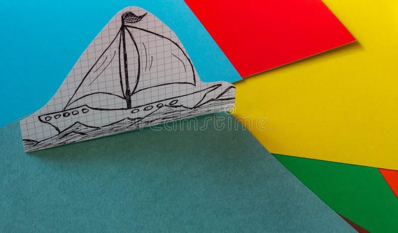 Ein einfaches Schiff gezeichnet auf Papierstände auf einer mehrfarbigen Pappe lizenzfreies stockfoto