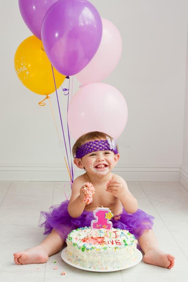 Ein Einjahresgeburtstagmädchen mit Kuchen stockbild