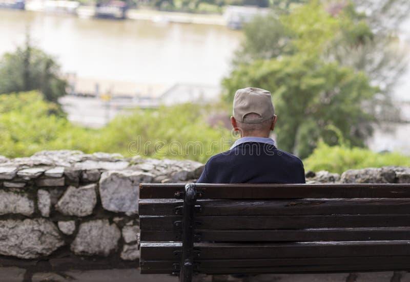 Ein einsamer alter Mann, der auf einer Bank in einem Park, Fluss betrachtend sitzt lizenzfreie stockfotografie