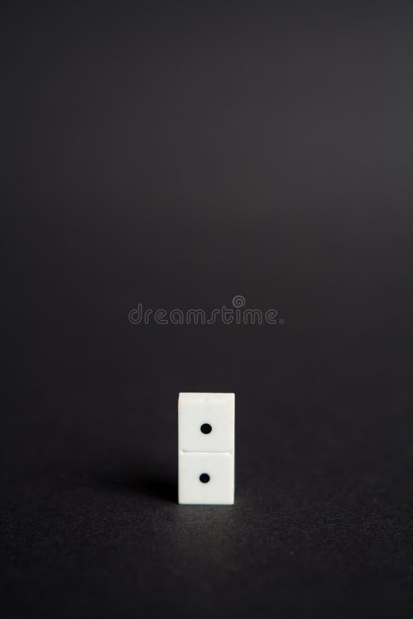 Ein einsamer dominoe Ziegelsteineinsamkeitskonzeptschwarzhintergrund stockfotografie