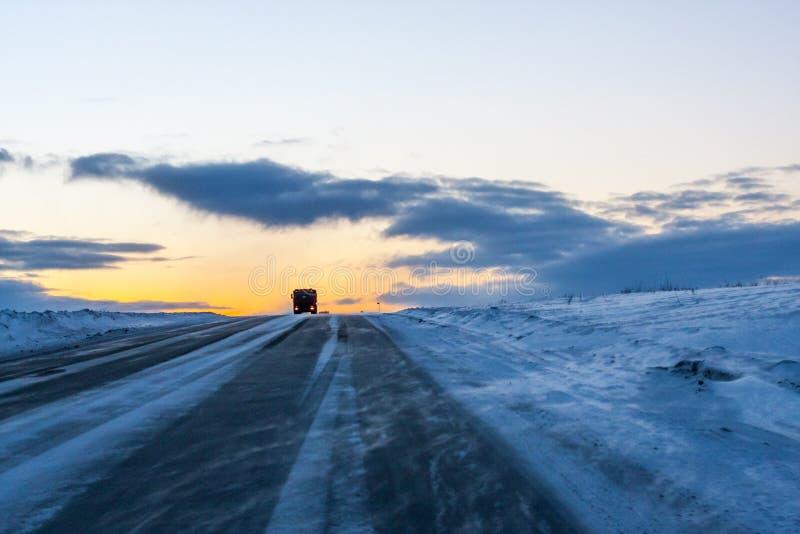 Ein einsamer Fernlastfahrer, der in den Blizzard an der Dämmerung fährt lizenzfreie stockfotos