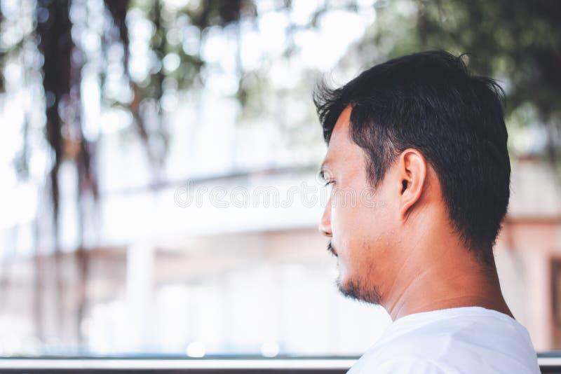 Ein einsamer Mann, der zurück sitzt und gegen unscharfen Hintergrund im Freien geistesabwesend ist stockfoto