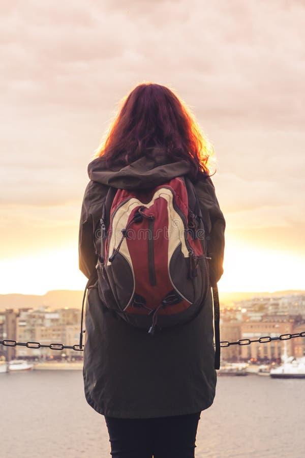 Ein einsames Mädchen mit einem Rucksack steht mit ihr zurück und betrachtet stockfoto