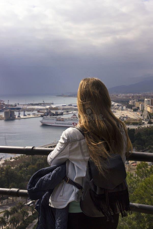 Ein einsames Mädchen steht auf einem Hügel und Blicken am schönen Panorama der spanischen Stadt von Màlaga an einem warmen sonnig lizenzfreie stockbilder