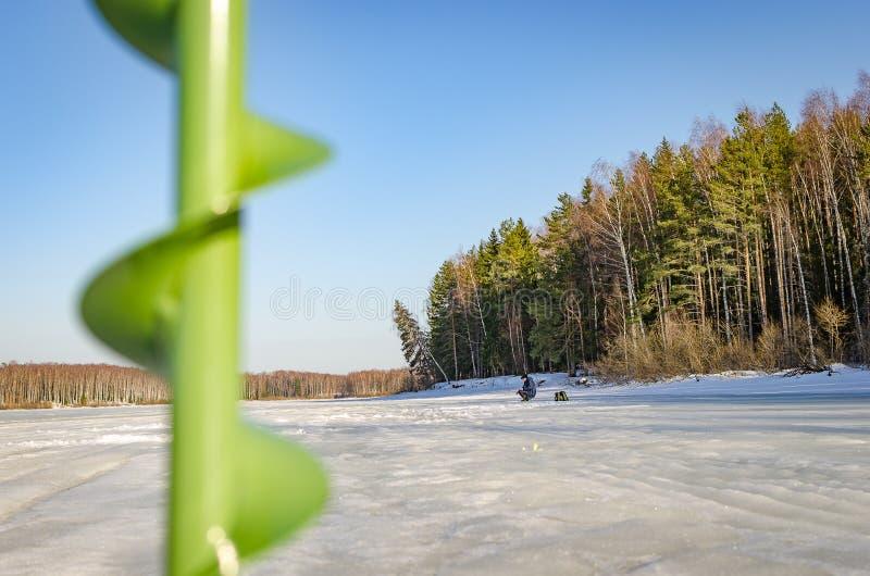 Ein einziger Fischer auf dem Eis des Flusses lizenzfreie stockfotos