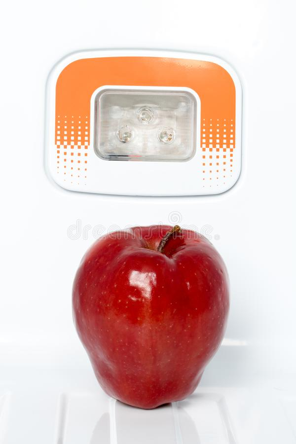 Ein einziger roter Apfel in einem Kühlschrank stockfotografie
