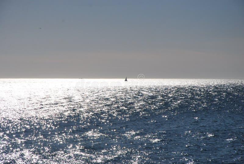 Ein einziges Segel-Boot im Meer lizenzfreie stockbilder