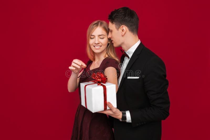 Ein eleganter Mann in einer Klage gibt einer Frau eine Überraschung, gibt ihr ein Geschenk, auf einem roten Hintergrund, das Konz stockfoto