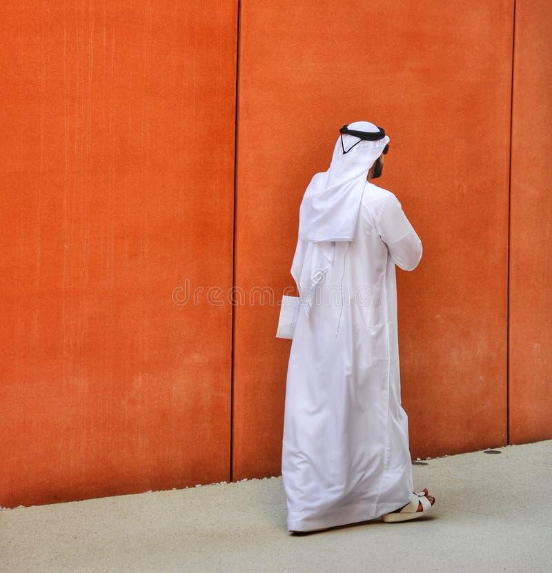 Ein eleganter Mann mit Sonnenbrille und arabischen Kleidern gehend auf die Straßen seines Landes Arabisches Ethniekonzept stockfotografie