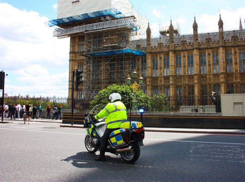 Ein englischer Polizist auf Kontrollen und Uhren eines Motorrades über dem Verkehr in zentralem London stockfotografie
