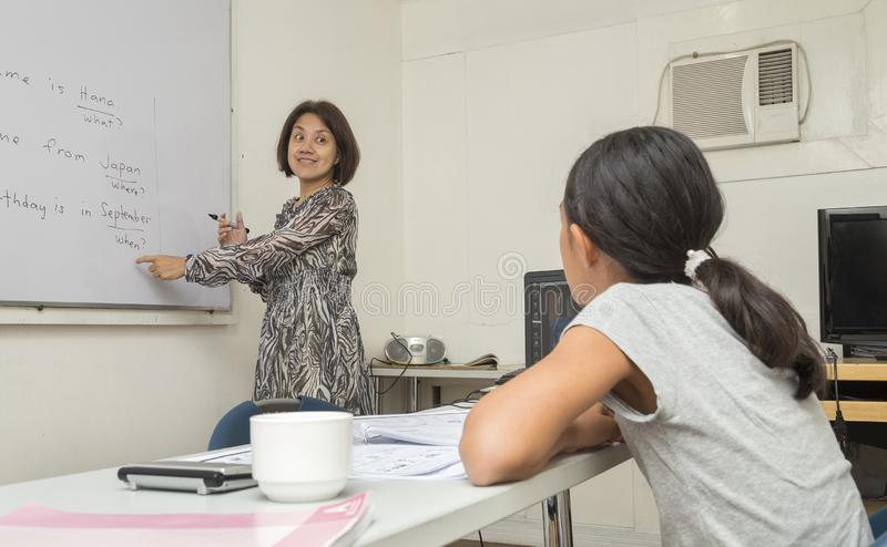 Ein englischer weiblicher Lehrer ist, erklärend schreibend und die Regeln von Englisch auf dem weißen Brett und unterrichtet ein  lizenzfreie stockfotografie