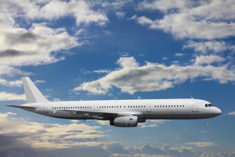 Ein enormes Passagierflugzeug in einem ruhigen Flug gegen einen Hintergrund von Wolken stockfotos