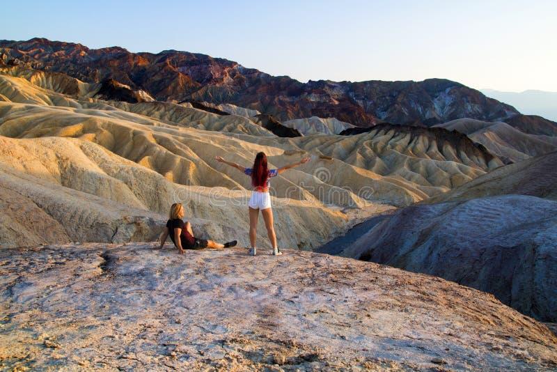 Ein entspanntes Paar von den Reisenden, die Ansicht von ruhigen alten abgefressenen Bergen genießen, gestalten an Zabriskie-Punkt lizenzfreies stockfoto