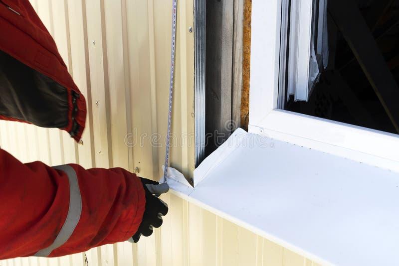 Ein Erbauer in den Handschuhen misst das Fenster draußen mit einem Maßband Berufshandwerker in einer roten Robe mit Maßen eines W lizenzfreie stockbilder