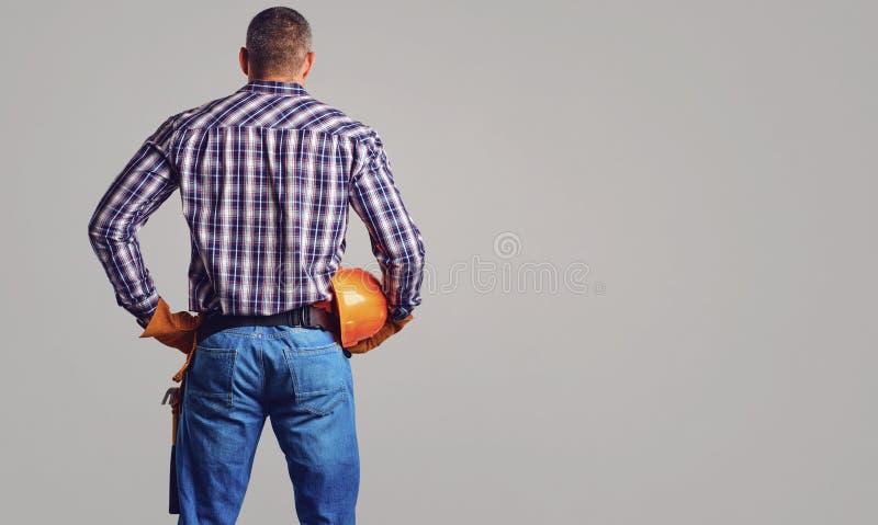 Ein Erbauermann mit einem Sturzhelm in seinen Händen zurück sehen an lizenzfreie stockfotografie