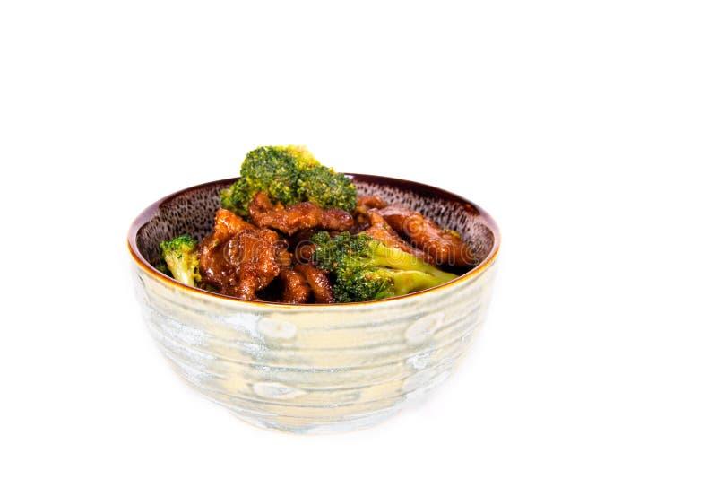 Ein Erdton maserte Schüssel auf einer weißen Tabelle, die mit Rindfleisch und Brokkoli Chineselebensmittel gefüllt wurde stockfotos