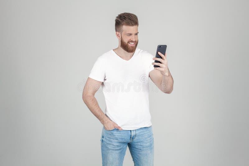 Ein erfüllter Mann mit einem üppigen Ingwerbart L?cheln zum Telefon Angekleidet in der zuf?lligen Kleidung Stand vor einem weißen stockfoto
