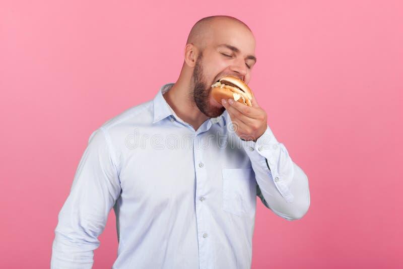 Ein erf?llter Mann mit einem ?ppigen Bart und ein Kahlkopf öffnet eine große Öffnung damit bald so möglich, seinen Burger zu esse stockfotos
