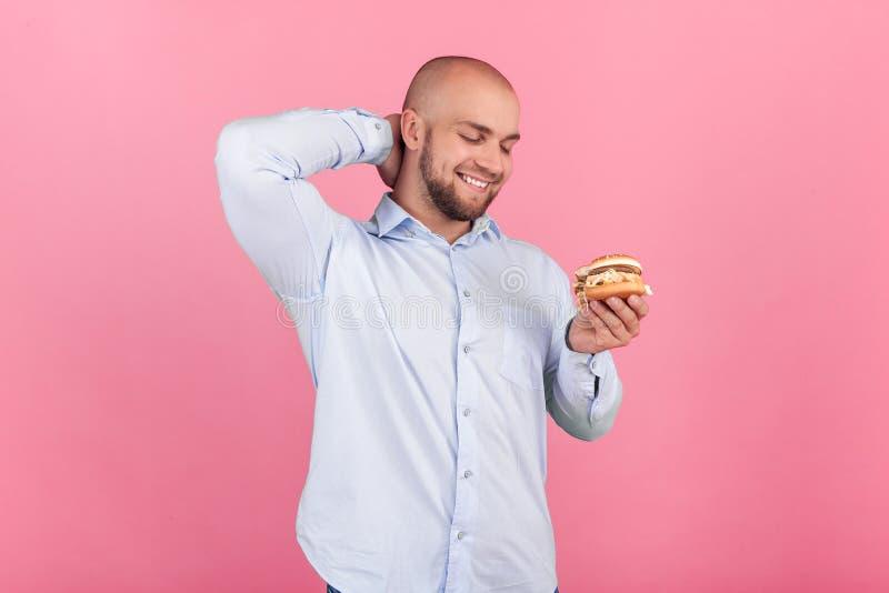 Ein erf?llter Mann mit einem ?ppigen Bart und ein Kahlkopf Blicke auf seinen Burger mit einem Durst, damit er so bald wie möglich lizenzfreies stockbild
