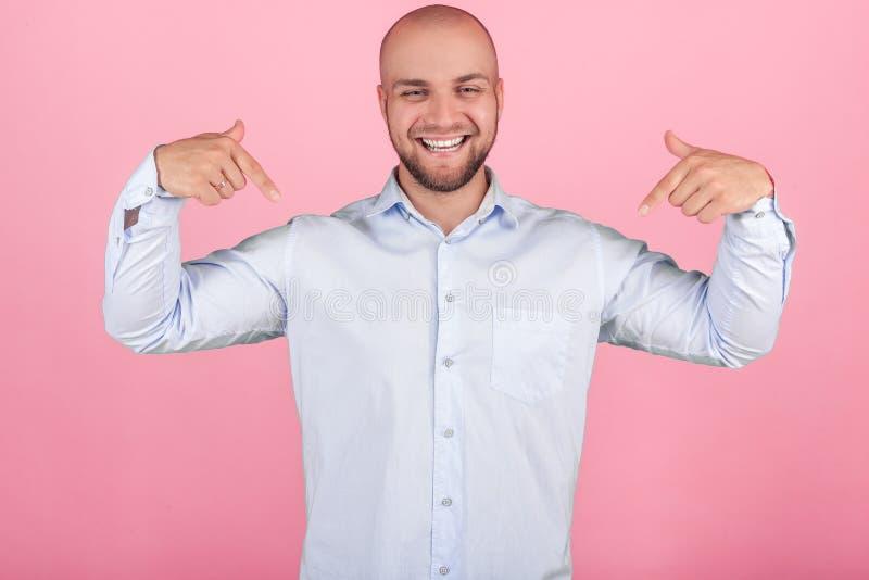 Ein erf?llter Mann mit einem ?ppigen Bart und ein Kahlkopf Zeigen auf selbst, wo Sie Ihr Logo oder Text setzen können angekleidet stockbild