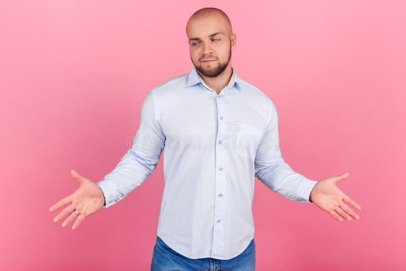 Ein erf?llter Mann mit einem ?ppigen Bart und ein Kahlkopf Zu Hände in den Seiten anheben kennt nicht, was geschieht angekleidet  stockbild