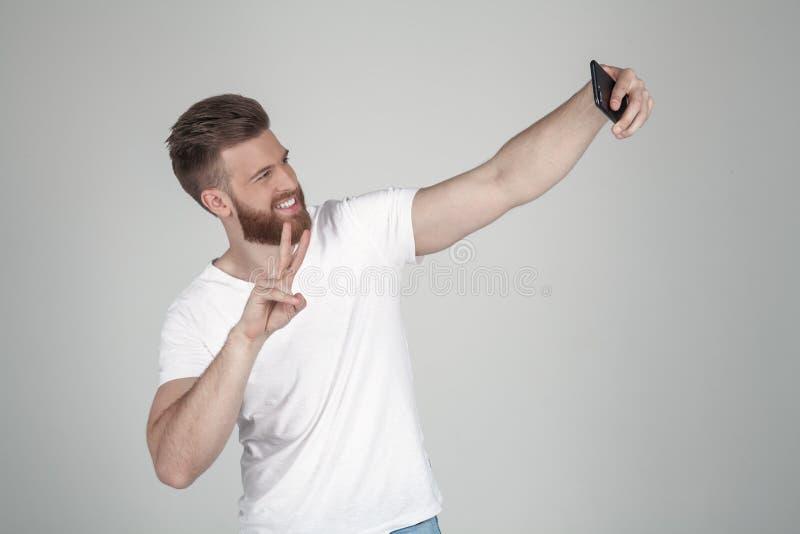 Ein erf?llter Mann mit einem ?ppigen Ingwerbart Macht ein sephi und stellt durch sein Handv-zeichen, zwei-fingriger Gruß dar Trag stockfotos