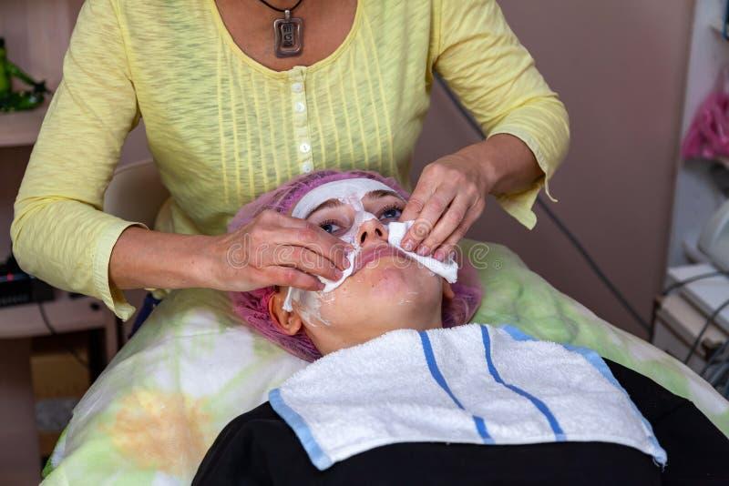 Ein erfahrener Cosmetologist wäscht weg eine Maske der weißen Creme auf dem Gesicht eines jungen Mädchens, das auf der Couch währ lizenzfreies stockfoto