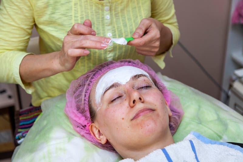 Ein erfahrener Cosmetologist wendet eine Maske der wei?en Creme auf dem Gesicht eines jungen M?dchens an, das auf der Couch w?hre stockfotos