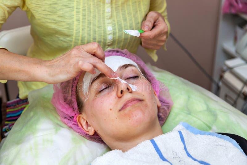 Ein erfahrener Cosmetologist wendet eine Maske der wei?en Creme auf dem Gesicht eines jungen M?dchens an, das auf der Couch w?hre lizenzfreie stockfotografie