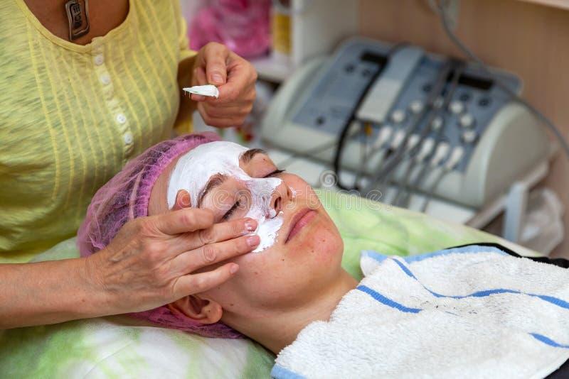 Ein erfahrener Cosmetologist wendet eine Maske der wei?en Creme auf dem Gesicht eines jungen M?dchens an, das auf der Couch w?hre stockfoto